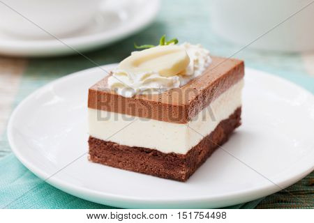 Three chocolate mousse cake on a white plate Outdoor background