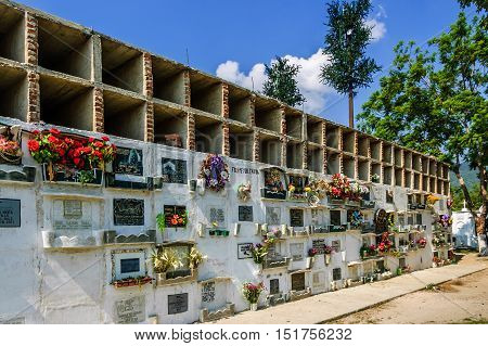 San Lazaro Cemetery Antigua Guatemala - May 6 2012: Flowers & wreaths cover mausoleum in cemetery in Spanish colonial town of Antigua