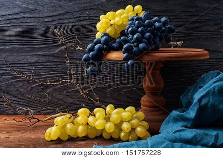 Still life with blue and green grapes on a background of black textured wood in a rustic style with copy space