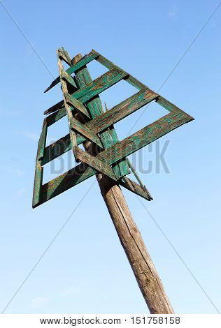 Old green sea mark used for naval navigation isolated on blue sky.