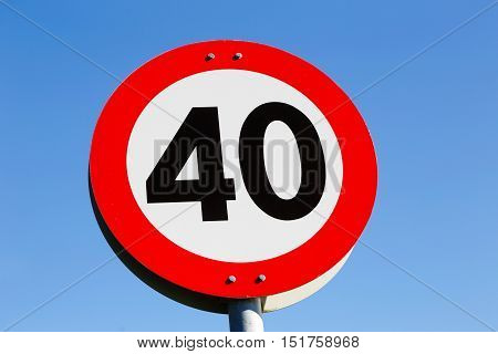 Norwegian road sign speed limit 40 isolated on blue sky.