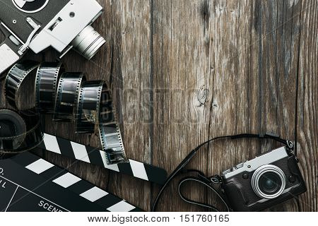 Vintage film camera clapper board filmstrip and old camera on a desktop cinema and videomaking concept