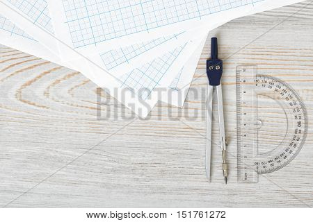 Layout with compass, protractor and graph paper on wooden surface in top view. Workplace of draftsman, architect, constructor or designer. Engineering work. Measurement. Tools for drawing.