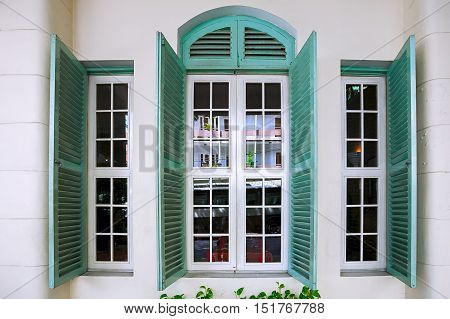 Old window with green shutters against the white walls.