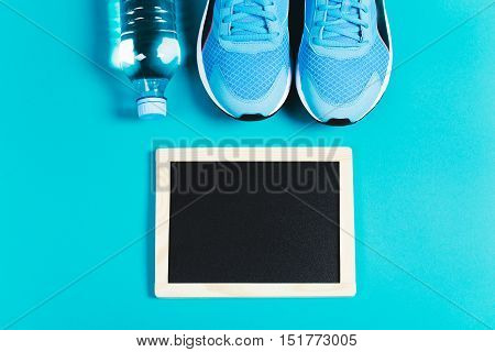 Fitness background made of sneakers, bottled water and clean chalkboard on blue background. Concept of healthy lifestile and food, everyday training and force of will. Flat lay style of picture