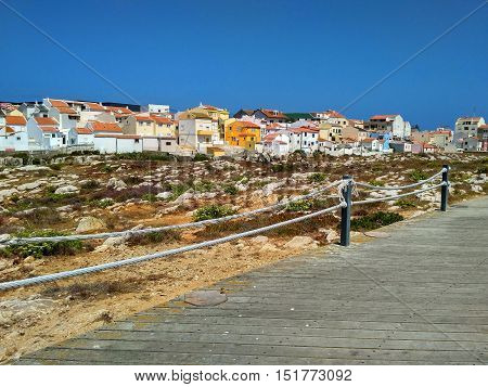 View to houses near ocean and wooden road in Peniche, Portugal