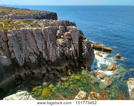 Cliffs with rocks and amazing color water in ocean coast of Peniche, Portugal