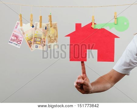 Concept of real estate and deal. Hand of seller man with house model and money banknotes. Selling and buying proposition.