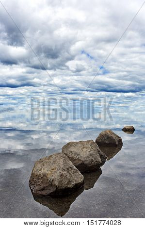 Serene balance of rocks leads gaze to the sky and clouds. Location is Lewis Lake in Yellowstone National Park in Wyoming. poster