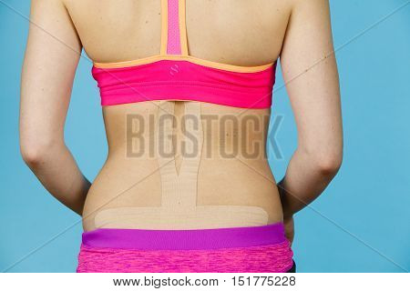 Woman with kinesiotaping application for back pain. Backache alternative kinesio tape therapy method. Health and body care.