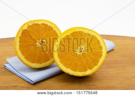 Still life of sliced orange halves on light blue napkin and oval wood board. Horizontal photo with copy space at top.