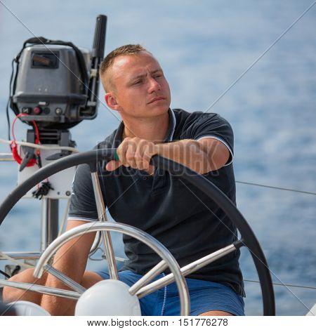 Skipper drive a sailing boat.