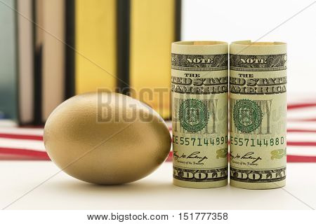 Gold nest egg next to American currency with books in background.