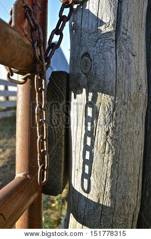 A corral gate casts shadows of the chain links unto the wooden post