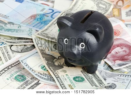 Black piggy bank on a pile of banknotes of various denominations and currencies.