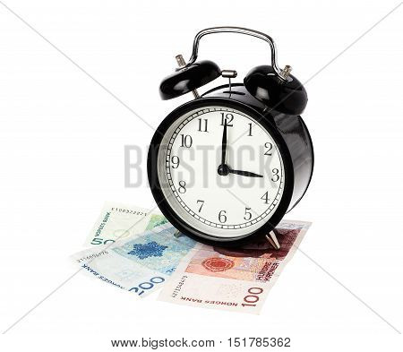 One black alarm clock displays three o clock on top of Norwegian banknotes isolated on white background.