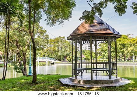 Open gazebo with seats beside the pond in public park