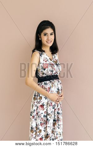 young pregnant model standing and her belly. Future mom expecting baby. Maternity concept. Copy space for text message