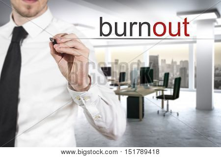 businessman in modern office writing burnout in the air