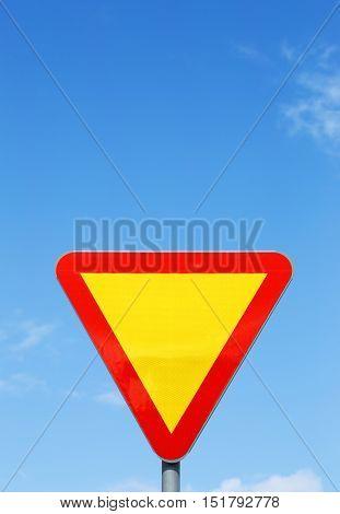 Swedish traffic sign Give Way on blue sky.