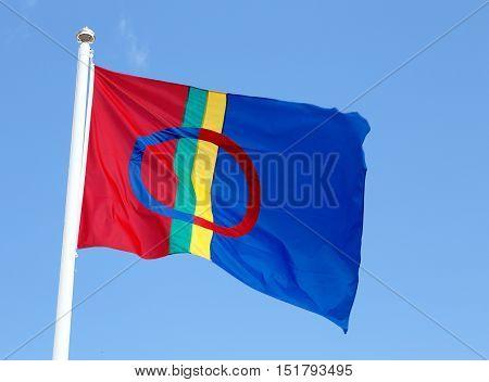 The Sami flag isolated on clear blue sky.