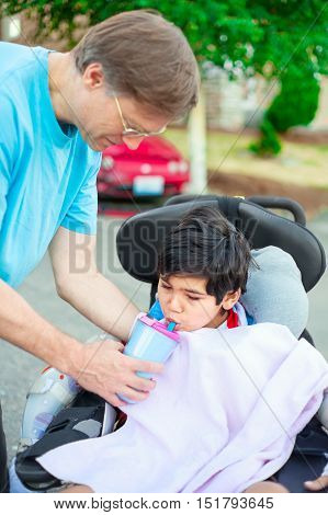 Father holding water cup helping disabled ten year old son in wheelchair drink from straw