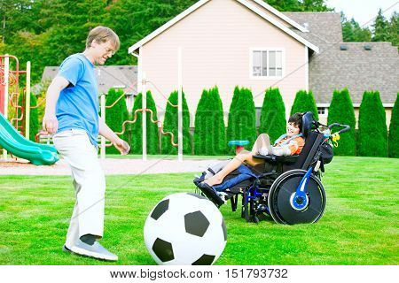Caucasian father playing soccer with ten year old biracial disabled son in wheelchair at park outdoors