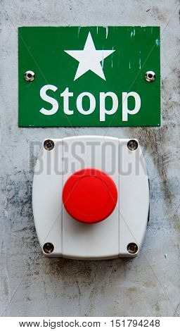 Red Swedish emergency stop button and sign.