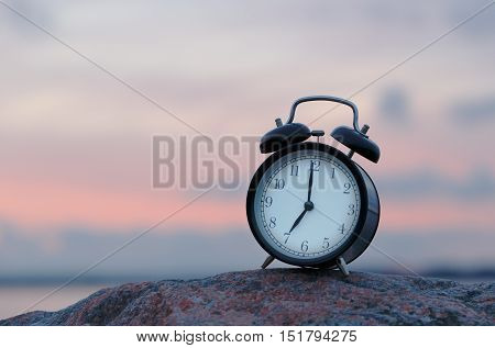 One black alarm clock on rock at seven o clock outdoor during sunrise.