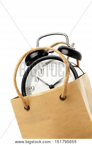 Cllose-ip of one black alarm clock inside a brown paper bagwith handles isolated on white.