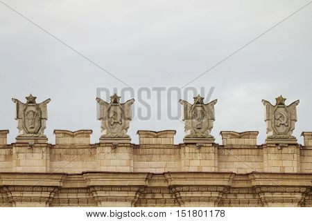 Fragment of parapet administrative government building with USSR symbols. Hammer and sickle. Typical pattern of Stalinist architecture.