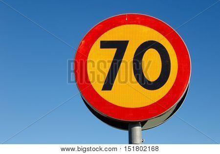 Sweddish speed limit sign 70 on blue sky.
