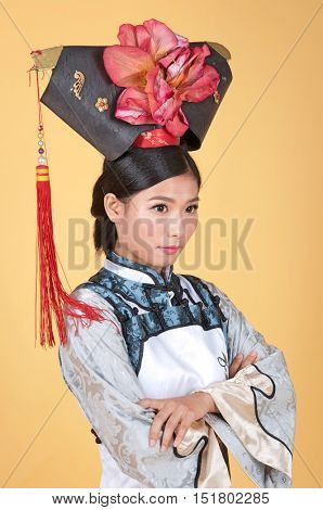 Beautiful Chinese princess with arms folded in traditional clothes in front of yellow background
