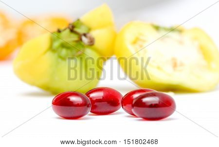 picture of a krill oil caspule in front of a small chili bell paprika on white background