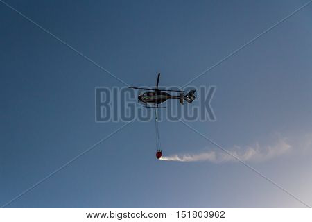 ROME - AUGUST 23: Firefighting helicopter carrying bucket containing water from Mediterranean Sea to put out fires on scrubland on August 23 2016 in Rome.