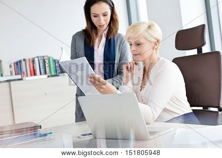 Businesswoman with female manager reading book at desk in office