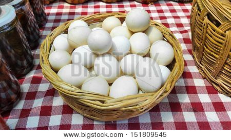 Chicken eggs in a basket on a chequered tablecloth