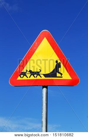 Swedish road sign beware of sledge dog team on blue sky.
