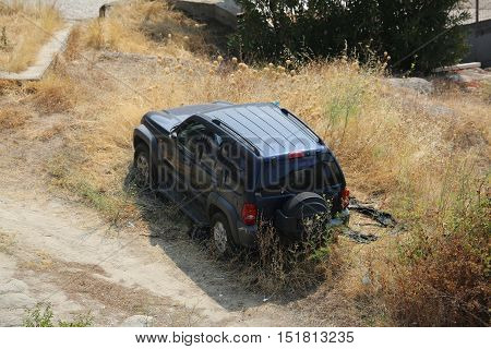 Kavala Greece - August 2 2016: Abandoned Beautiful Black Jeep Cherokee SUV in a Field in Kavala Greece