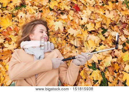 season, technology and people concept - beautiful young woman lying on ground and autumn leaves and taking picture with smartphone selfie stick