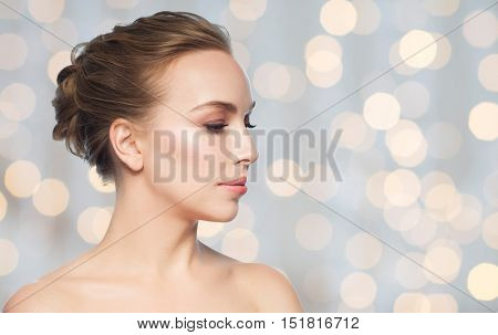 health, people, plastic surgery and beauty concept - beautiful young woman face over holidays lights background