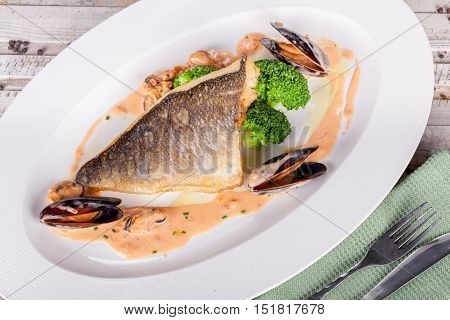 Fish fillet with seafood sauce on white plate