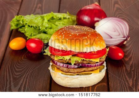 Double beef burger with ingridients on wood background