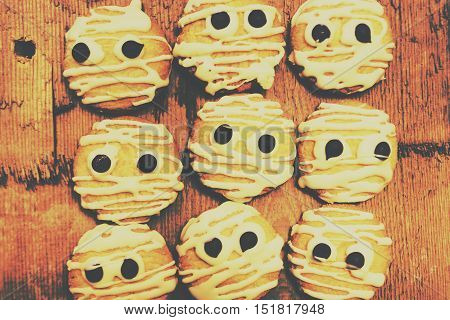 Retro toned baking batch of creepy and kooky cookie mummies with all with scary looks of halloween fear