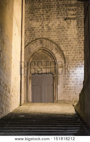 Girona (Gerona Catalunya Spain): old typical street by night. Door of gothic church