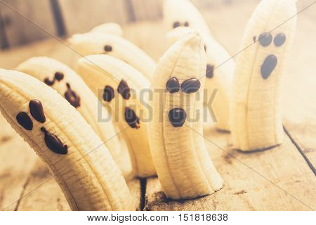 Ghostly banana monsters with choc face details sliding in haunted halloween scene. Spooky seasonal snacks
