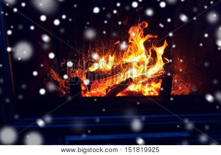 winter, christmas, warmth, fire and coziness concept - close up of burning fireplace with snow