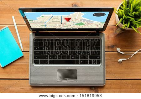 navigation, location, and technology concept - close up of laptop computer with gps navigator map on screen on wooden table