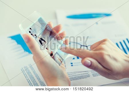 business, technology, news, mass media and people concept - close up of woman hand holding transparent smartphone with web page on screen at office