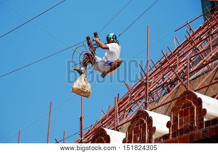 Nakon Pathom Thailand - January 9 2010: Worker slides down a cable from the 120 meter high great chedi covered with scaffolding during restoration work at Wat Phra Pathom Chedi  *